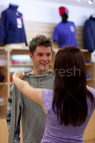 Stock photo: Bright couple looking for a sweat-shirt in a clothes store