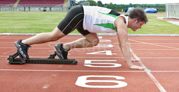 Handsome sprinter on the starting line putting his foot in the starting block in a stadium Stock photo © wavebreak_media