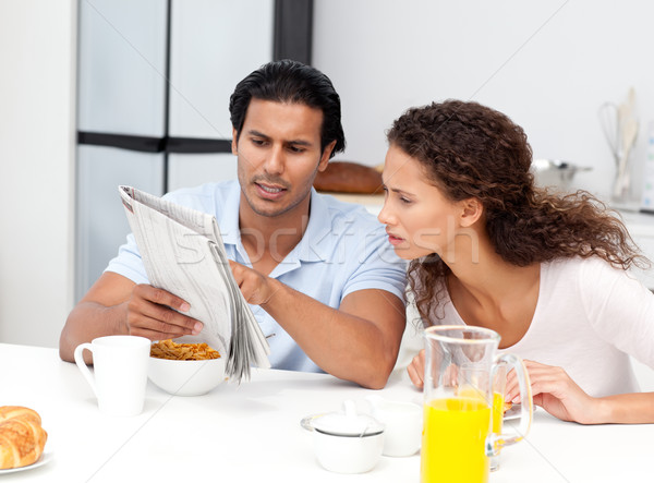 Serious man showing the newspaper to his wife during breakfast at home Stock photo © wavebreak_media