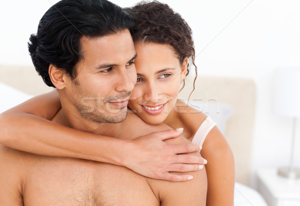 Lovely couple hugging sitting together on their bed Stock photo © wavebreak_media