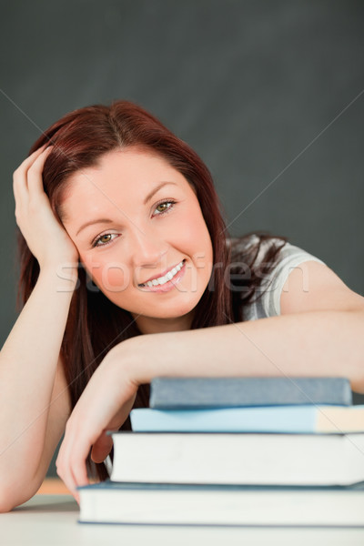 Portrait of a smiling young student with her forearm on her books in a classroom Stock photo © wavebreak_media