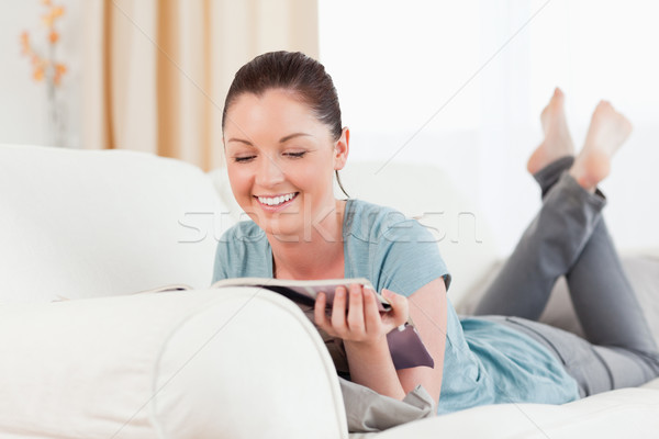 Stock photo: Lovely woman reading a magazine while lying on a sofa in the living room