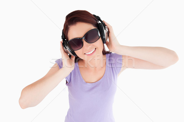 Red-haired Woman with headphones and sunglasses in a studio Stock photo © wavebreak_media