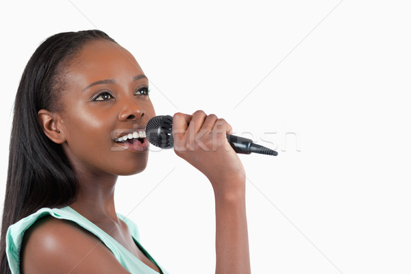Woman with microphone singing against a white background Stock photo © wavebreak_media