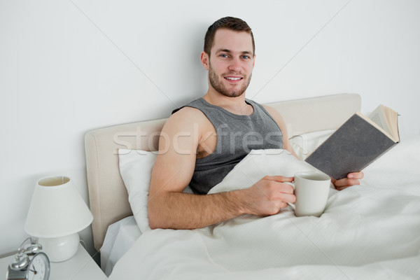 Young man reading a novel while drinking a coffee in his bedroom Stock photo © wavebreak_media