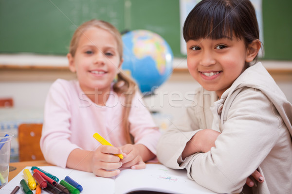 Smiling schoolgirls drawing while looking at the camera in a classroom Stock photo © wavebreak_media