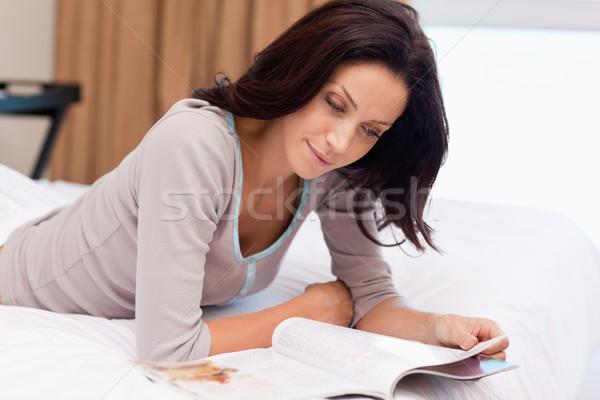 Młoda kobieta czytania magazyn bed szczęśliwy domu Zdjęcia stock © wavebreak_media