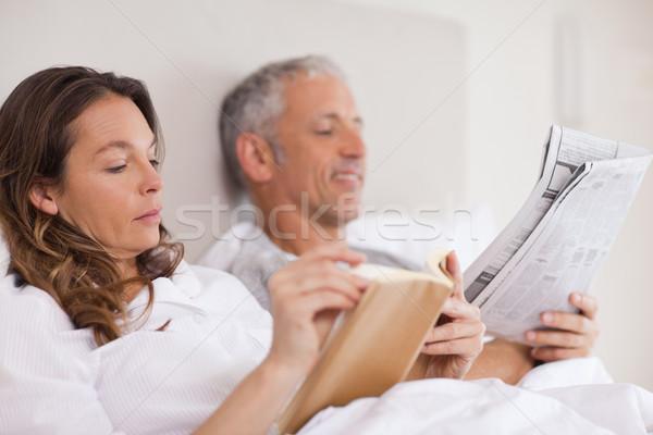 Kobieta czytania książki mąż gazety sypialni Zdjęcia stock © wavebreak_media