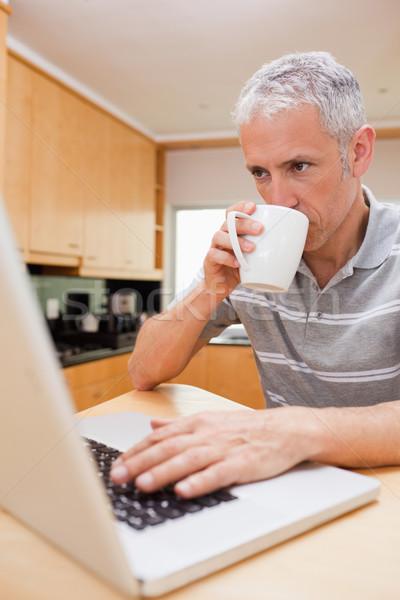 ストックフォト: 肖像 · 男 · ラップトップを使用して · 飲料 · コーヒー · キッチン