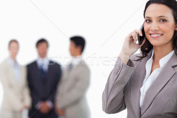 Mosolyog elarusítónő mobiltelefon kollégák mögött fehér Stock fotó © wavebreak_media