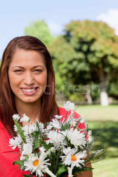Young woman with the sun shining on her face, looking ahead while holding a bunch of flowers Stock photo © wavebreak_media