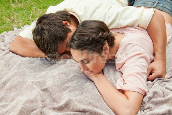 Man with his arm around his female friend while they are lying prone on a grey blanket int the grass Stock photo © wavebreak_media