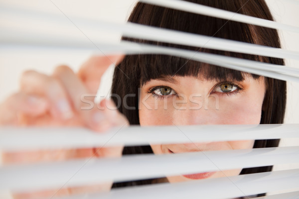 A smiling woman moving her blinds to see better Stock photo © wavebreak_media