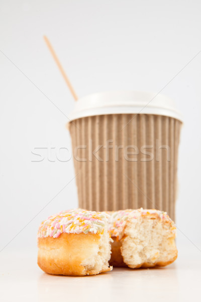 An half eaten multi coloured doughnut and a cup of tea placed together against a white background Stock photo © wavebreak_media