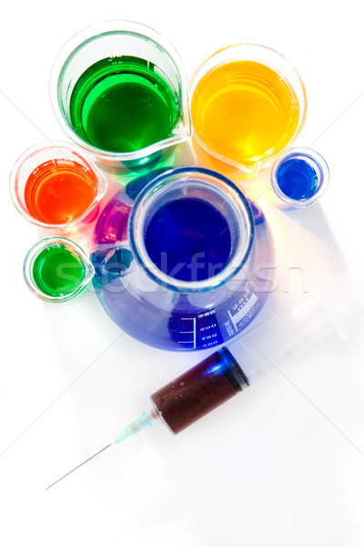 Various beakers and erlenmeyer with a syringe against a white backgroud Stock photo © wavebreak_media