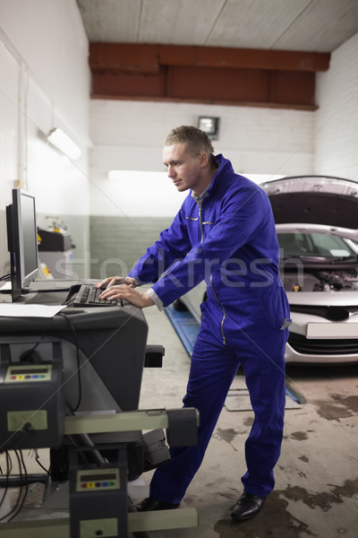 Concentrated mechanic using a computer in a garage Stock photo © wavebreak_media