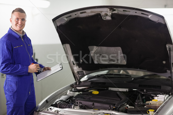 Smiling mechanic holding a clipboard in a garage Stock photo © wavebreak_media