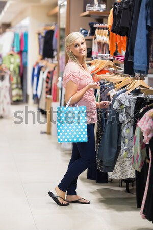 Woman is standing at the clothes rack looking at clothes at the boutique  Stock photo © wavebreak_media