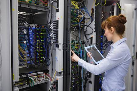 Woman fixing wires of servers in data center Stock photo © wavebreak_media
