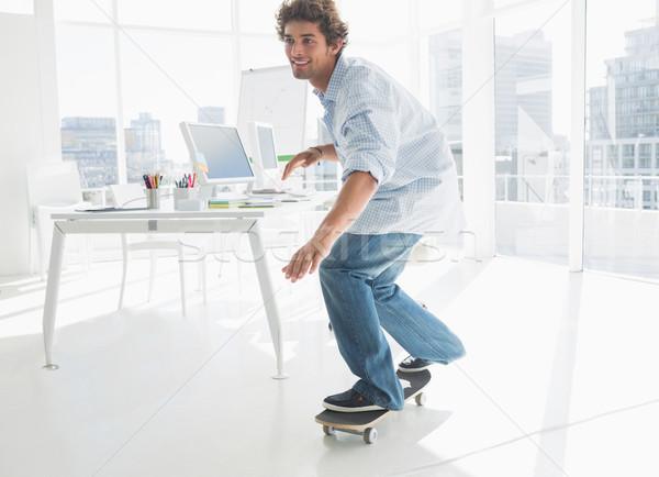 Heureux jeune homme skateboard bureau lumineuses Photo stock © wavebreak_media