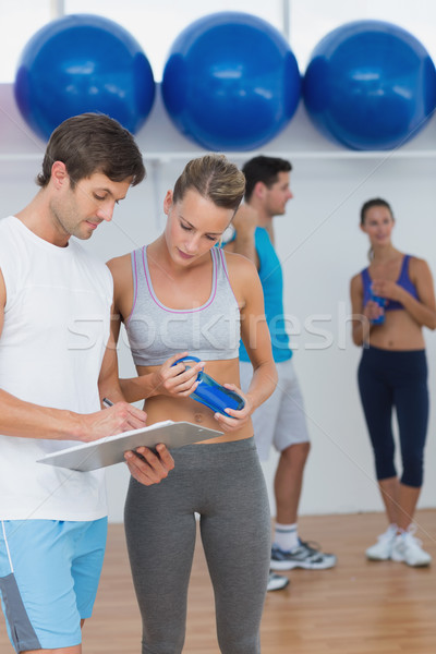 Couple looking at clipboard with fitness class in background Stock photo © wavebreak_media