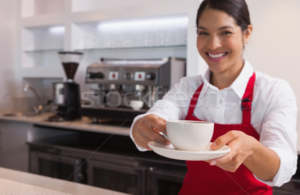 Happy young barista offering cup of coffee smiling at camera Stock photo © wavebreak_media
