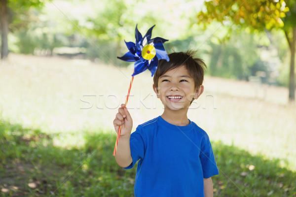 Happy cute little boy holding pinwheel at park Stock photo © wavebreak_media