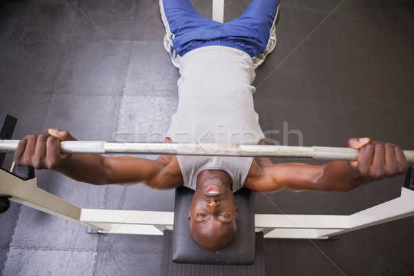 Muscular man lifting barbell in gym Stock photo © wavebreak_media