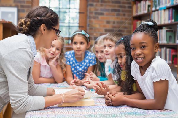Bonitinho alunos professor leitura biblioteca escola primária Foto stock © wavebreak_media