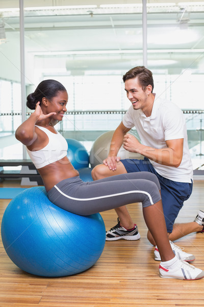 Personal trainer working with client on exercise ball Stock photo © wavebreak_media
