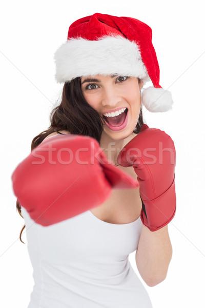 Festive brunette in boxing gloves punching Stock photo © wavebreak_media