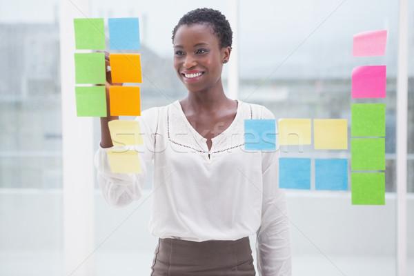 Smiling businesswoman writing on sticky notes on window Stock photo © wavebreak_media