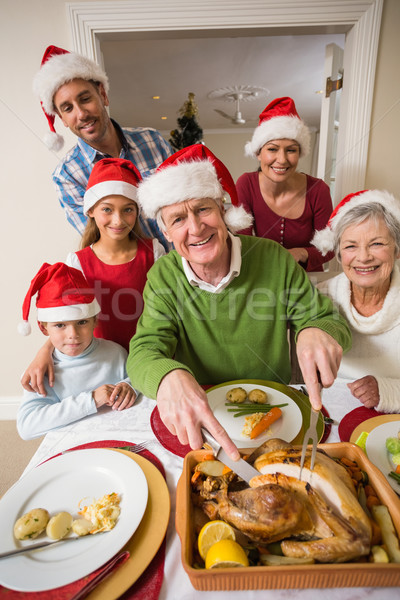 Grandfather in santa hat carving chicken at christmas dinner Stock photo © wavebreak_media