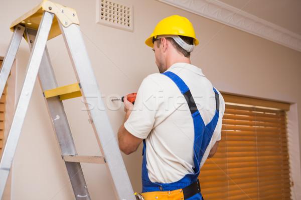 Construction worker drilling hole in wall Stock photo © wavebreak_media