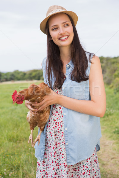 Happy brunette holding her chicken Stock photo © wavebreak_media