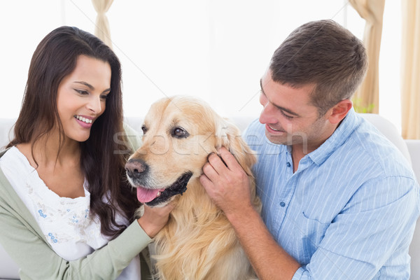 Couple stroking dog at home Stock photo © wavebreak_media
