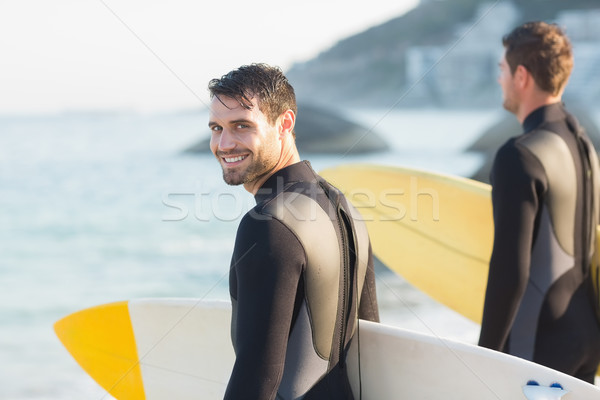 Two men in wetsuits with a surfboard on a sunny day Stock photo © wavebreak_media