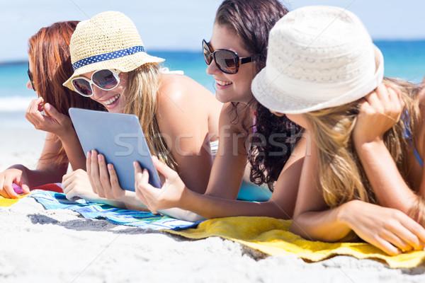 Happy friends wearing sun glasses and using tablet Stock photo © wavebreak_media