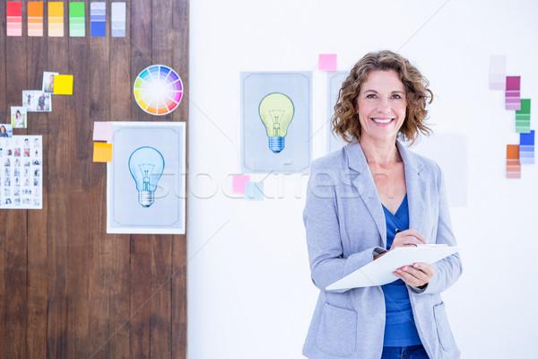 Creative businesswoman looking at camera and taking notes  Stock photo © wavebreak_media