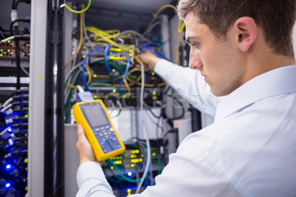 Serious technician using digital cable analyzer on server Stock photo © wavebreak_media