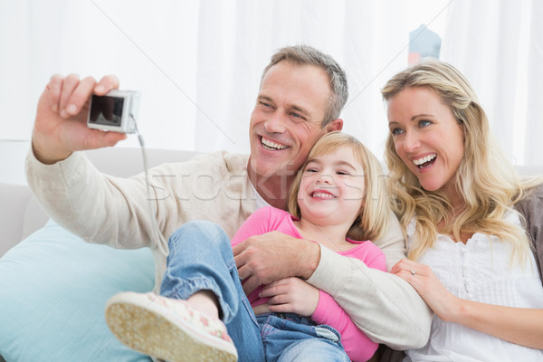 Cheerful family taking self pictures with a digital camera Stock photo © wavebreak_media