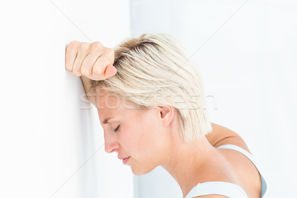 Sad blonde woman with her head on wall  Stock photo © wavebreak_media