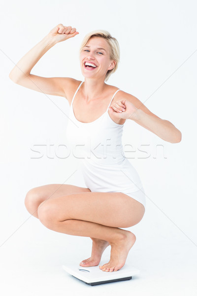 Happy attractive woman crouching on a scales Stock photo © wavebreak_media