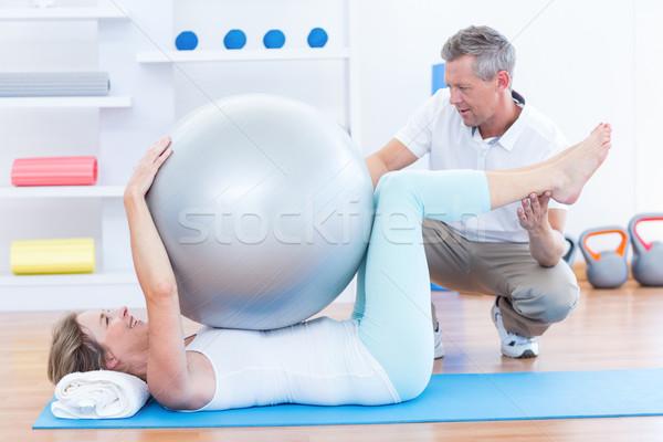 Terapeuta pomoc pacjenta wykonywania piłka medycznych Zdjęcia stock © wavebreak_media
