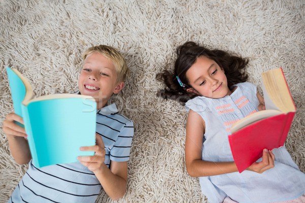 Siblings lying on rug and reading book in living room Stock photo © wavebreak_media
