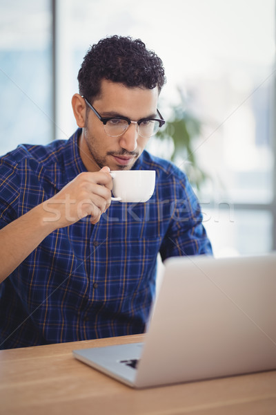 Attentive executive having coffee while using laptop at desk Stock photo © wavebreak_media
