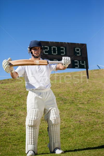 Confident cricketer with bat standing on field Stock photo © wavebreak_media