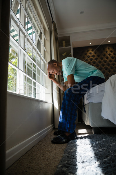 Full length side view of serious senior man sitting on bed by window Stock photo © wavebreak_media