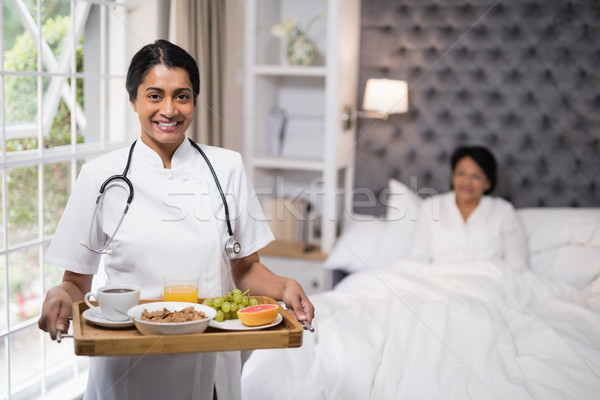 Nurse holding breakfast tray while patient lying on bed at home Stock photo © wavebreak_media
