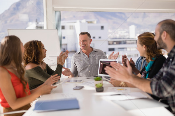 Stock photo: Colleagues applauding man while presentation